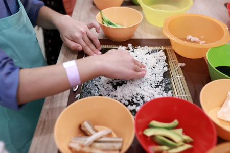 Cook spreading sushi rice over nori on bamboo mat