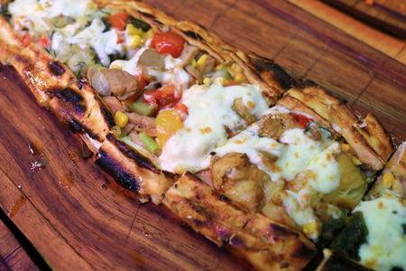 Sebzeli Pide dish on wooden board in restaurant