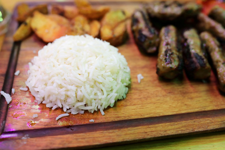 Rice and kebabs on wooden board in restaurant