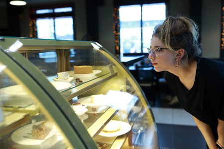 Teen looking at showcase with desserts in cafe