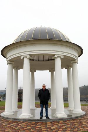 Man posing on background of rotunda in autumn