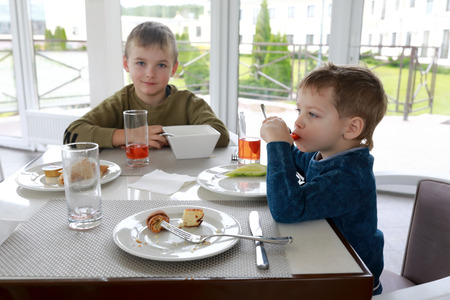 Two boys have breakfast in a restaurant