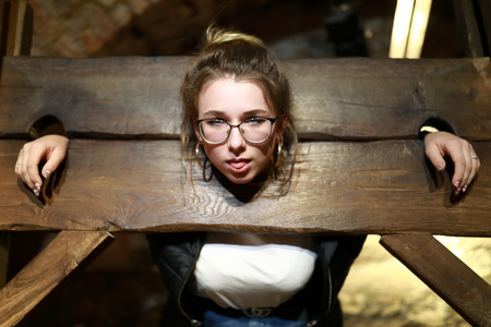 Portrait of girl in a wooden pillory