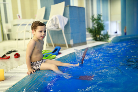 Child in flippers sitting on edge of pool
