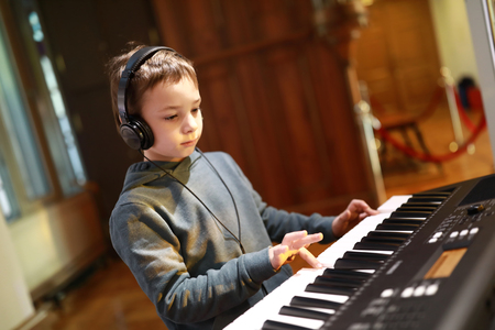 Boy with headphones playing on a synthesizer in music class