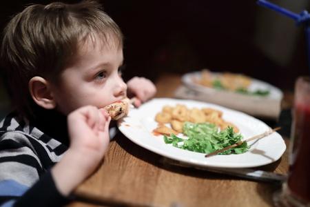 Boy has kebab on skewer in restaurant