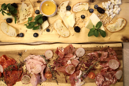 Set of cheeses and ham on wooden plates