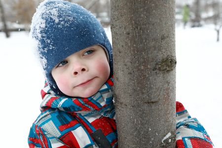 Child hugging tree trunk in winter park