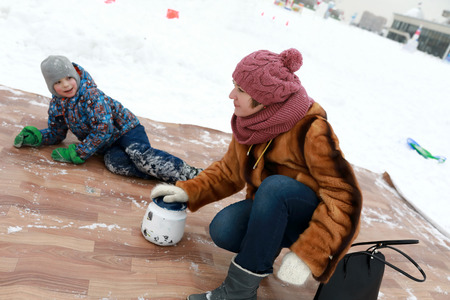 Mother with her son playing curling with kettles in winter