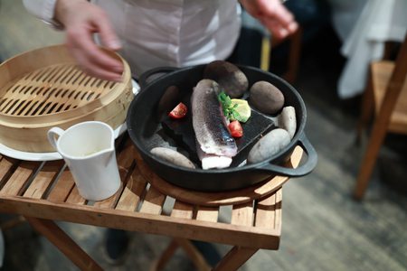 Cooking whitefish in a pan with stones