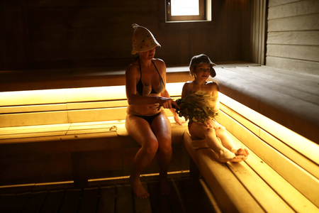 Mother and her son in steam room of Russian bath