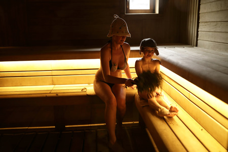 Mother with her son resting in steam room of Russian bath