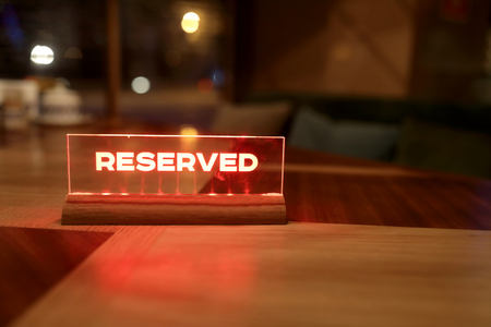 Glowing red sign reserved on a table