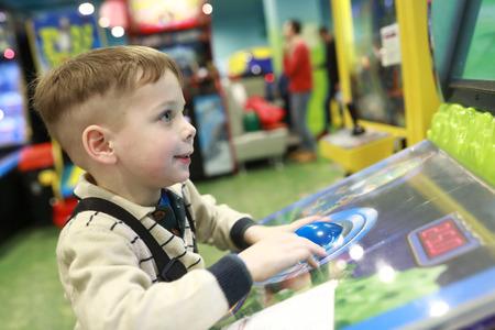 Boy plays arcade game in indoor amusement park Imagens