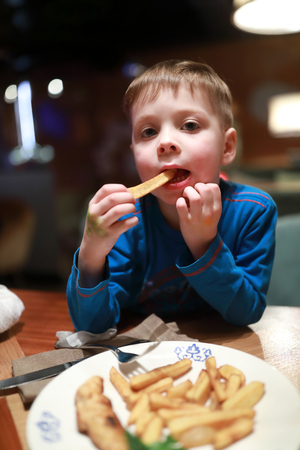Child eating fried potatoes in the restaurant