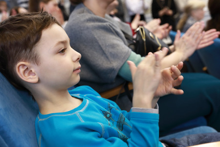 Portrait of child applauds in the theater