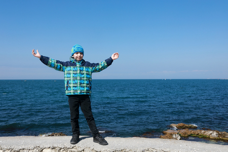 Portrait of kid on black sea background in spring