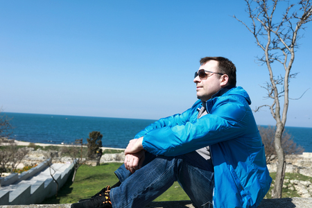 Man sitting on embankment of Chersonesos, Sevastopol 免版税图像