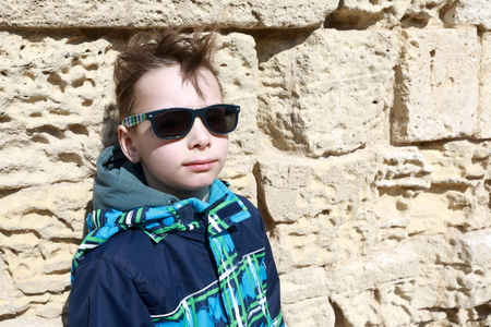 Child on background of stone wall in Chersonesos