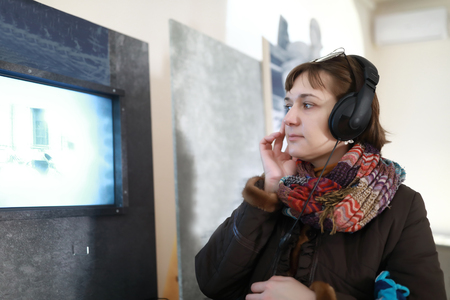Serious woman in headphones watching movie on vintage screen