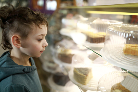 Child choosing cake on showcase in cafe Banque d'images - 123920377