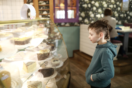 Boy choosing cake on showcase in cafe Banque d'images - 123920385