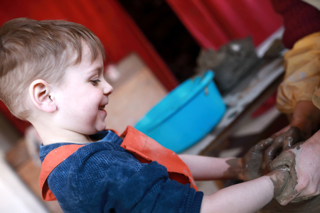 Happy child at potters wheel in workshop