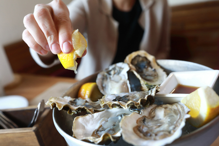Woman sprinkles oysters with lemon juice in restaurant 版權商用圖片