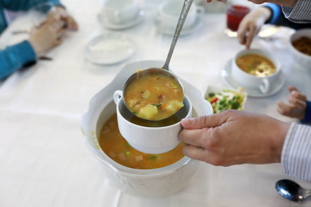 Person pouring soup into bowl in restaurant