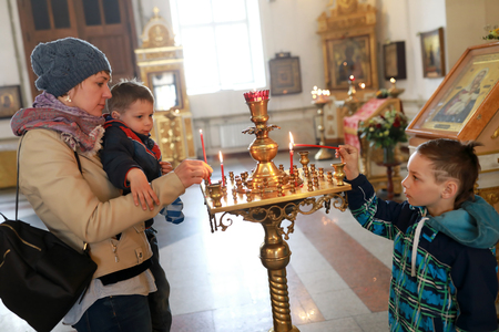 Mother and sons light candles in russian orthodox church Stock Photo
