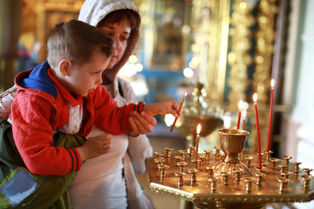 Mother with son put candles in the Russian Orthodox Church