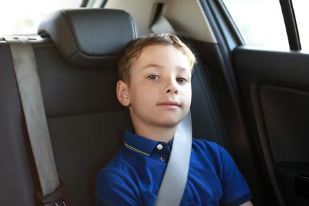 Kind sitzt auf dem Rücksitz des Autos