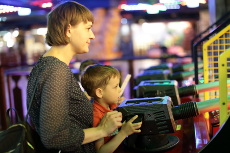 Portrait of mother and son playing in amusement center Imagens