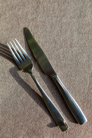 Knife and fork on tablecloth in restaurant