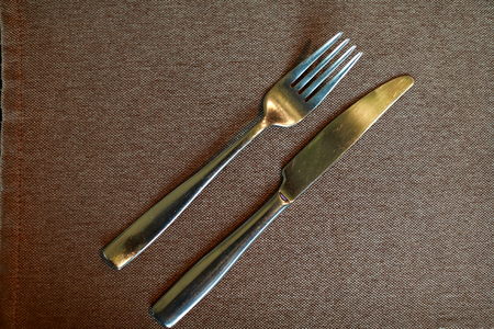 Fork with knife on tablecloth in restaurant
