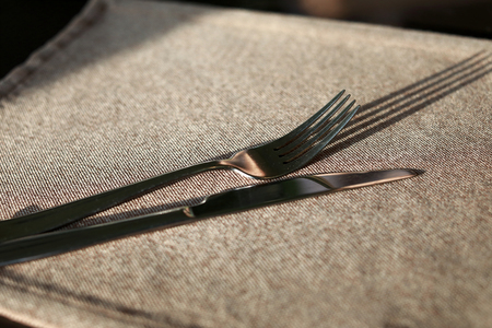 Knife with fork on tablecloth in restaurant