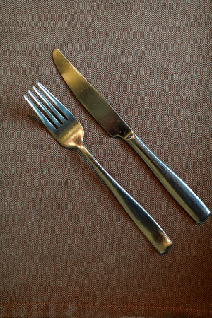 Fork and knife on tablecloth in restaurant