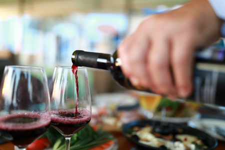 Person pouring red wine in a restaurant Фото со стока