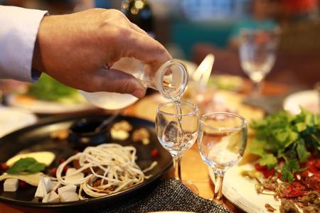 Person pouring vodka into glass in restaurant