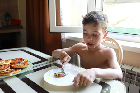Child eating cheesecakes for breakfast at home