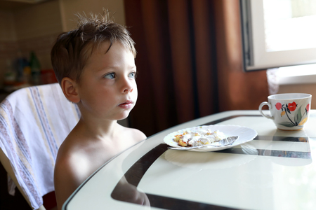 Boy eating cheesecakes for breakfast at home