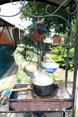 Man cooking fish soup in pot on fire