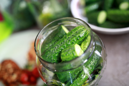 View of pickling cucumbers in glass jar at home