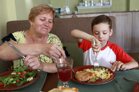 Grandmother and grandson have lunch in restaurant
