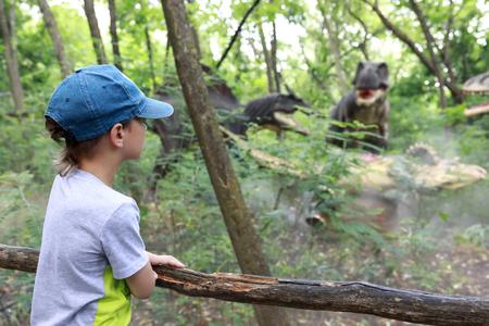 Child looking at dinosaur in summer park 写真素材