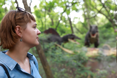 Woman looking at dinosaur in summer park 写真素材
