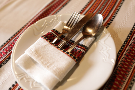 Fork with knife and spoon in embroidered napkin