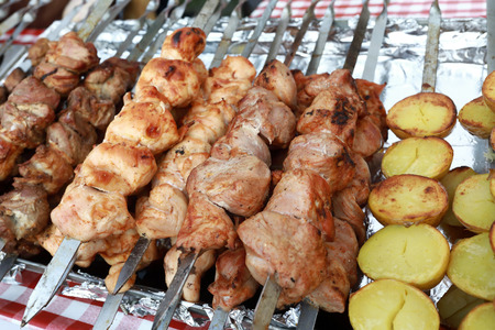 Various meat and patato kebabs on skewers on market counter