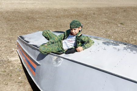 Boy lying on inverted boat in summer