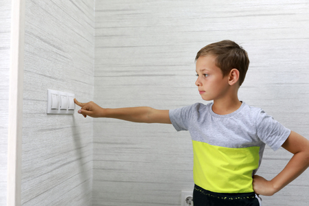 Child turns off the light at home